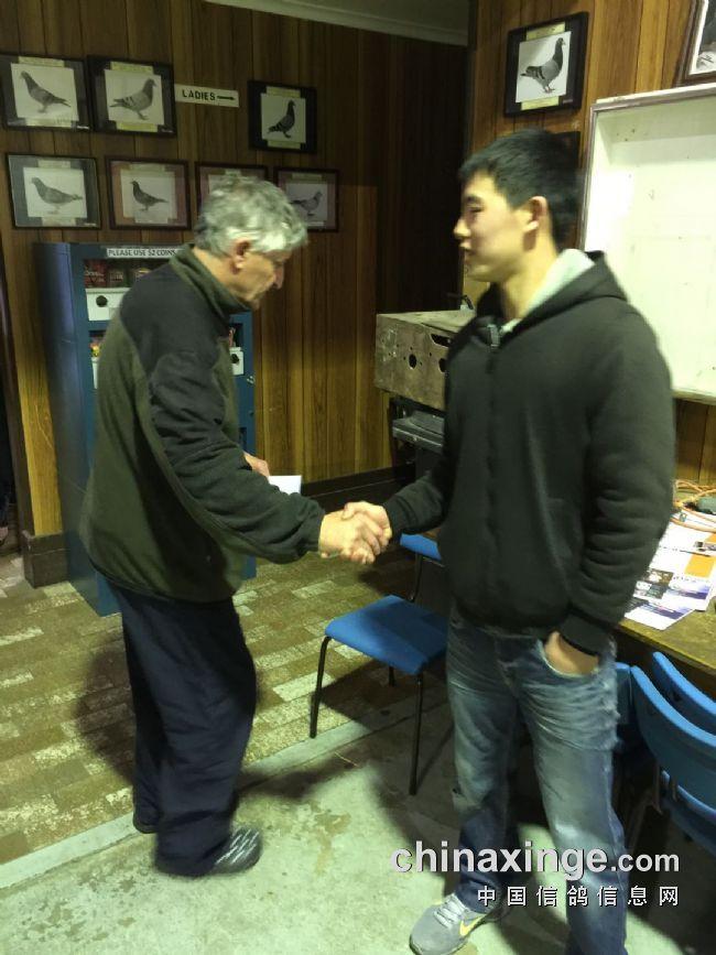 俱乐部老会长与冠军鸽友少游握手祝贺